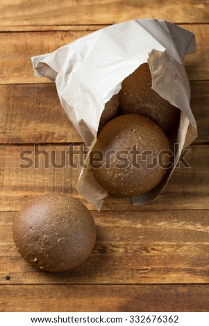 Rye bread in paper bag on wooden background. Close up. Horizontal - stock photo