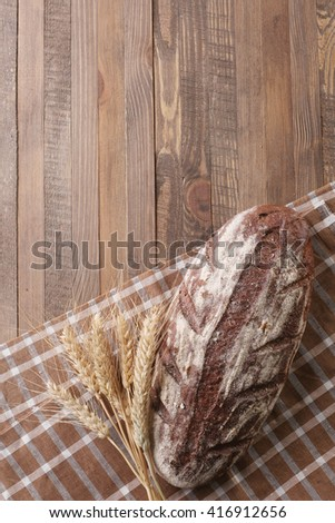 rye bread on a napkin, ears rye on background of wooden planks - stock photo