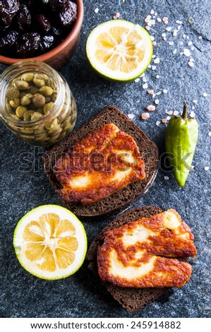 Rye bread sandwiches with fried halloumi cheese, sun-dried olives in bowl, lemon, capers and pepper on gray stone background - stock photo