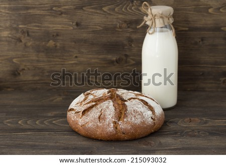 Rye bread with milk on wooden background - stock photo