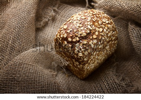 Rye bread with oat flakes on sacking - stock photo
