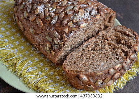 Rye bread  with pumpkin seeds. Freshly baked savory pastry  is on the yellow cloth napkin. Product is lower in gluten than your average white loaf and reduces body weight compared to wheat. - stock photo