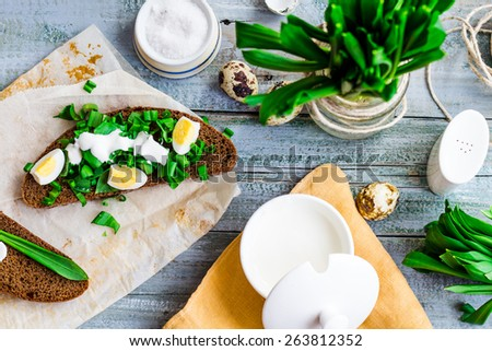 rye bread with wild garlic, sour cream and quail eggs, snack, toast on the gray board,top view - stock photo