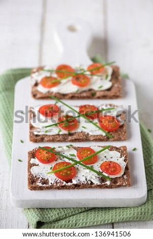 Rye crackers with cream cheese & sliced tomato served on a chopping board - shallow dof - stock photo