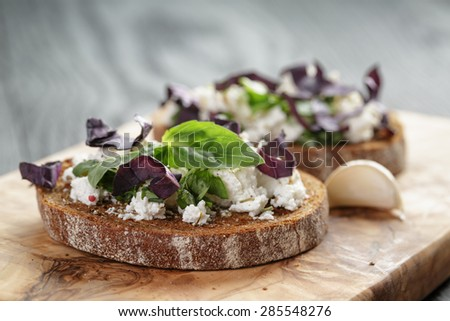 rye sandwich or bruschetta with ricotta, herbs and basil on wooden table - stock photo