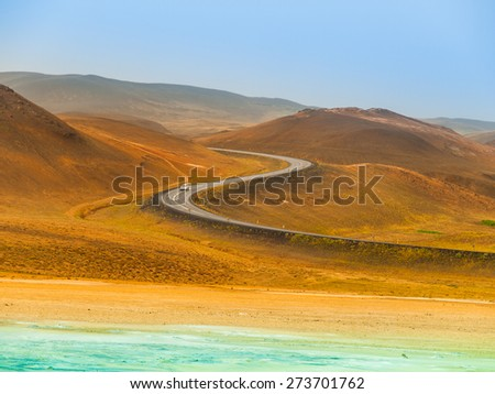 S-curve road with a car in northern Iceland - stock photo