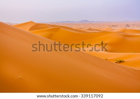 Saara dunes with a cloudy background cause by sand in strong wind. - stock photo
