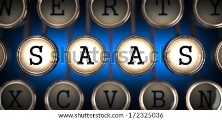 SAAS - Software-as-a-Service - on Old Typewriter's Keys on Blue Background. - stock photo