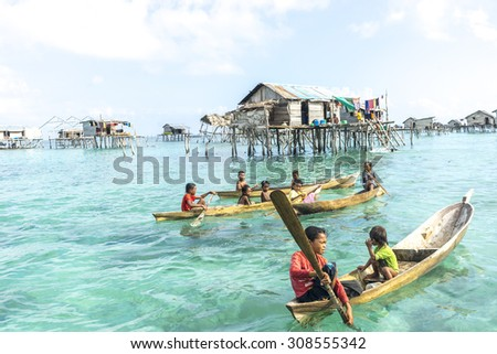 SABAH, MALAYSIA - AUGUST 15, 2015 : Unidentified Bajau Laut kids on a boat in Bodgaya Island. They lived in a house built on stilts in the middle of sea, boat is the main transportation here.  - stock photo