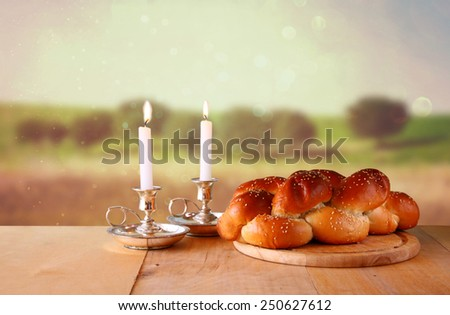Sabbath image. challah bread and candelas on wooden table  - stock photo