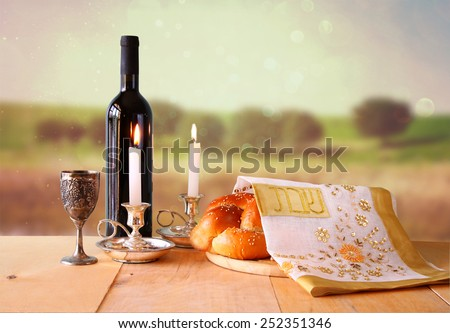 Sabbath image. challah bread, sabbath wine and candelas on wooden table.  - stock photo