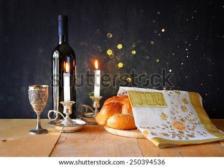 Sabbath image. challah bread, sabbath wine and candelas on wooden table. glitter overlay  - stock photo