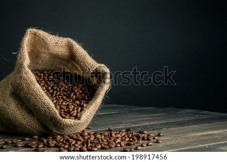 sack made by jute full of coffee beans,scattered on a wooden table - stock photo
