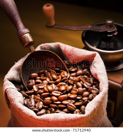 Sack of coffee beans and scoop. On a dark yellow background.