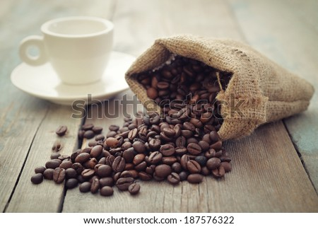 Sack of coffee beans with cup on wooden background closeup