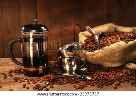 Sack of coffee beans with french press and cups - stock photo