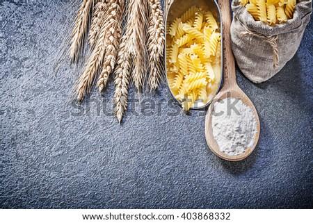 Sack short-cut macaroni kitchen scoop wood spoon flour wheat rye ears on black background. - stock photo