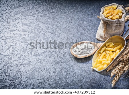 Sacking bag uncooked macaroni kitchen scoop wood spoon flour wheat rye ears on black background copy space. - stock photo