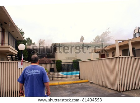 SACRAMENTO, CA - AUGUST 28: Apartment resident watches firefighters cut through roof to release smoke and fire from blaze raging in adjoining apartment August 28, 2010 in Sacramento, California. - stock photo