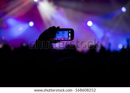 SACRAMENTO, CA - DECEMBER 2013: Fan records Fall Out Boy on mobile phone during 107.9 The End's 2013 Jingle Ball at Sacramento's Memorial Auditorium in Sacramento, California on December 21, 2013 - stock photo