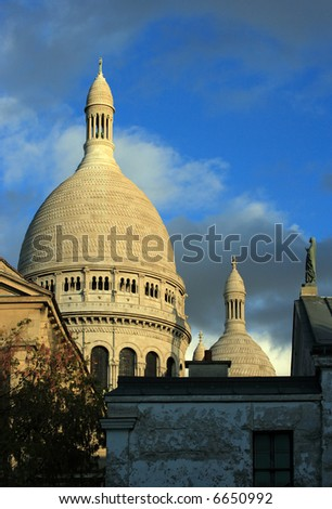 Sacre Coeur in Paris, France, as the sun begins to lower. - stock photo