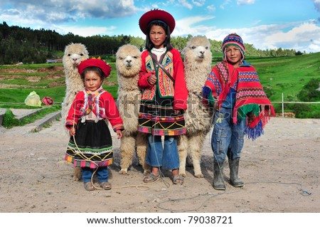 SACSAYHUAMAN, CUSCO, PERU - MARCH 08: Peruvian children in traditional dresses standing in row with small Alpacas on March 08, 2010 in Sacsayhuaman, cusco, peru. - stock photo