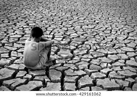 Sad a boy sitting on dry ground black and white tone .drought - stock photo