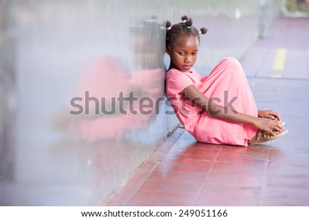 Sad african girl sitting and deeply thinking on the school floor. - stock photo