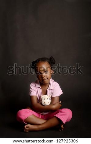 Sad African little girl alone on black background - stock photo