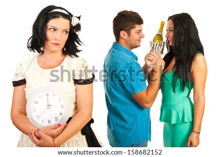 Sad alone woman holding clock while other people celebrating new year - stock photo