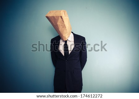 sad and ashamed businessman with bag over head - stock photo