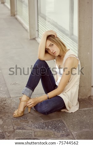 sad and beautiful woman sitting near the building in the city
