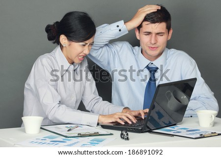 sad and depressed businessman and woman sitting at table during meeting - stock photo