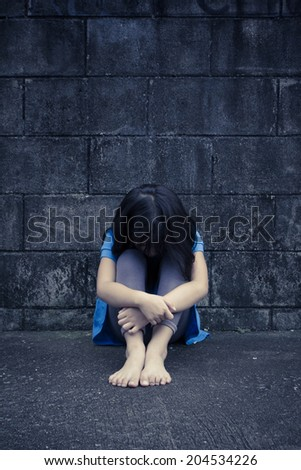 sad and depressed little Asian girl sitting in grunge room - stock photo