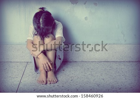 sad and depressed little girl sitting near the wall  - stock photo