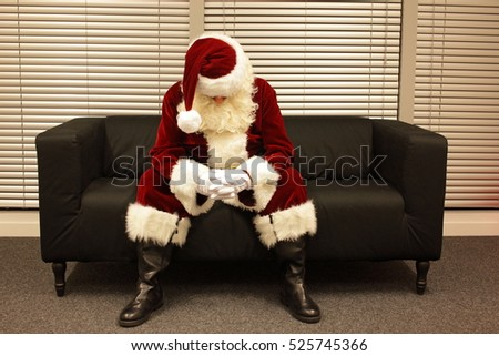 Sad and depressed Santa Claus waiting for christmas job sitting on sofa in his office