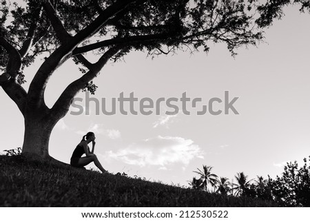 Sad and depressed woman deep in thought outdoors - stock photo