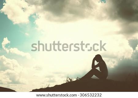 Sad and depressed woman sitting alone - stock photo