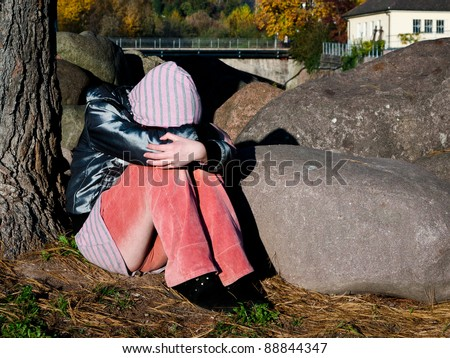 Sad and lonely girl sitting under a tree hiding her face - stock photo