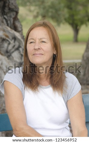 Sad and lonely looking middle aged woman sitting on park bench with worried or depressed facial expression and blurred background outdoor.