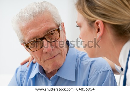 Sad and lonely senior man with nurse - stock photo