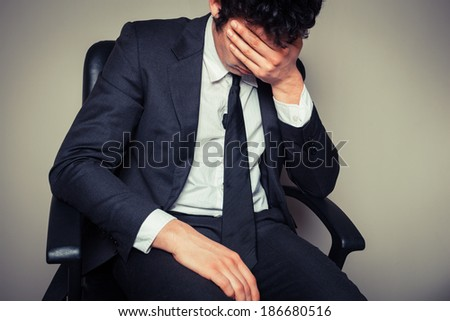 Sad and tired businessman is sitting in an office chair - stock photo