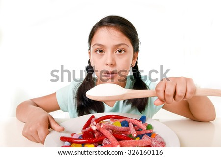 sad and vulnerable hispanic female child eating dish full of candy and gummies holding sugar spoon in wrong dangerous diet and sweet nutrition abuse and excess isolated on white background - stock photo