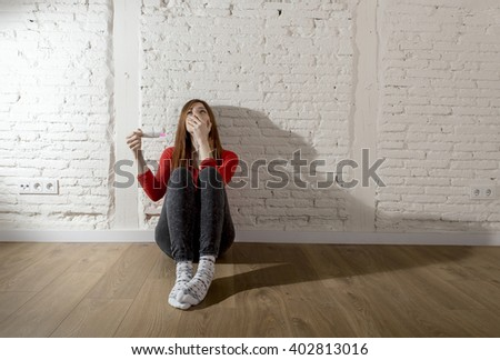 sad and worried pregnant teenager girl or young desperate woman holding positive pink pregnancy test looking scared and devastated at home floor in unwanted baby and unexpected motherhood - stock photo