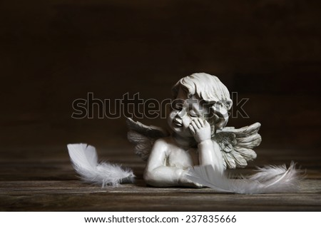 Sad angel with white feathers on a dark background for bereavement. - stock photo