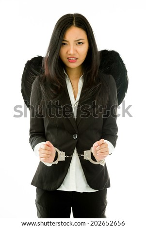 Sad Asian young businesswoman dressed up as black angel handcuffs isolated on white background - stock photo