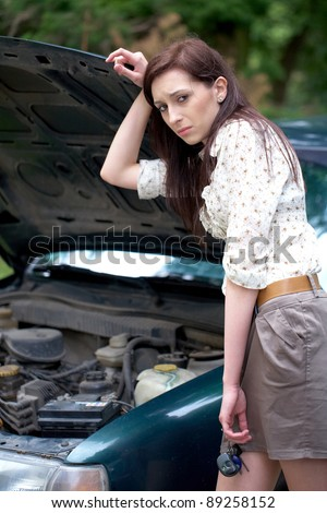 sad attractive brunette in front of her car broken down car, assistance concept - stock photo