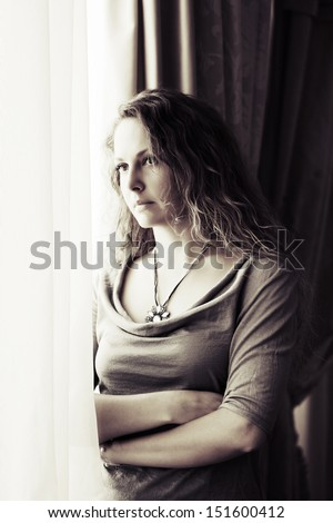 Sad beautiful woman looking out the window - stock photo