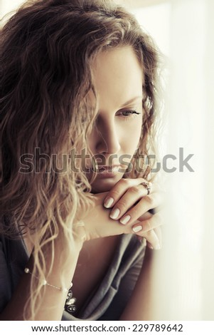 Sad beautiful woman with long curly hairs daydreaming  - stock photo