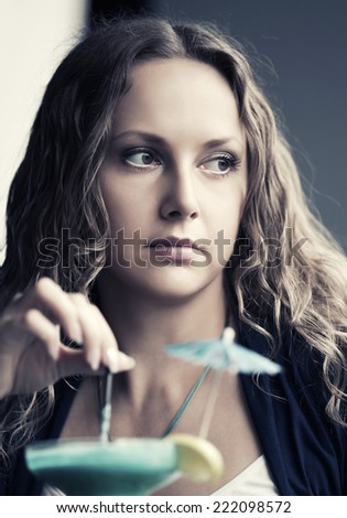 Sad beautiful young woman with cocktail at restaurant  - stock photo